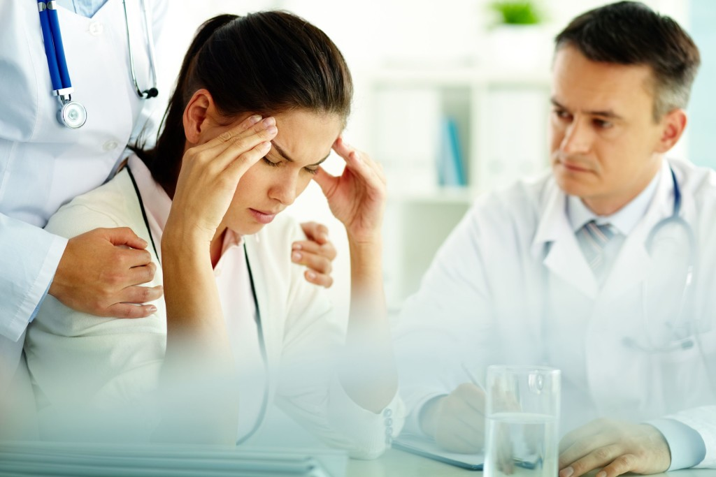 female patient headache with doctor copy